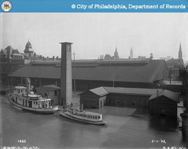 exterior of B&O train station during historic 1902 flood, boats float above the rail yard